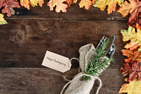 Silverware and burlap napkin with Happy Thanksgiving card over rustic fall background of autumn leaves. Image shot from overhead. Stock Photo