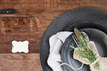 Tied bundle of Rosemary Herbs, Silverware and burlap napkin with black place setting over rustic wooden table made of weathered barn wood. Image shot from overhead. Blank place card for your text. Stock Photo
