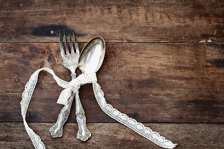 Antique silverware spoon and fork tied with lace ribbon over a rustic old wooden background with a grunge like feel. Image shot from overhead. Banco de Imagens