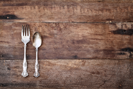 Antique silverware spoon and fork over a rustic old wooden background. Image shot from overhead. Banco de Imagens