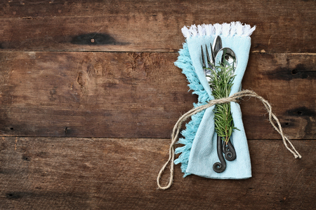 Silverware tied into a blue napkin over a rustic old wooden background. Image shot from overhead. Banco de Imagens