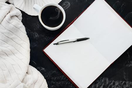 Coperta morbida maglia maglione con una tazza di caffè caldo e un libro aperto con la penna su sfondo lavagna sgangherata con spazio per copia spazio. Girato da sopra la testa.