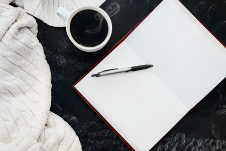 Soft knit sweater blanket with a hot cup of coffee and an open book with pen over grungy chalkboard  background with room for copy space. Shot from overhead. Stockfoto