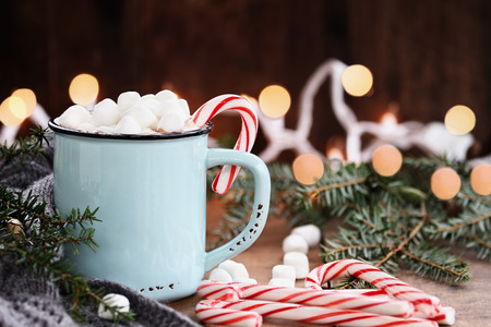 Enamel cup of hot cocoa with mini marshmallows and candy canes with pine boughs and gray scarf against a rustic background with beautiful Christmas lights of bokeh. Could also be coffee. Stock Photo