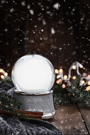 christmas lights background: Rustic image of an empty snow globe surrounded by pine branches, cinnamon sticks and a warm gray scarf with gently falling snow flakes.