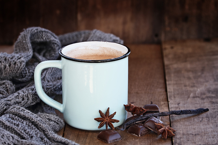 Enamel cup of hot cocoa or coffee for Christmas with chocolate bars, vanilla pod, spices and gray scarf against a rustic background. Shallow depth of field with selective focus on drink. Stock Photo