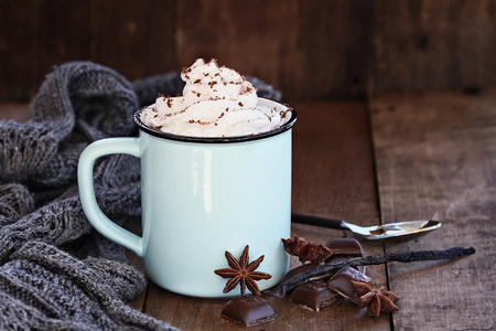 Enamel cup of hot cocoa or coffee for Christmas with whipped cream, shaved chocolate, vanilla pod, spices and gray scarf against a rustic background. Shallow depth of field with selective focus on drink.