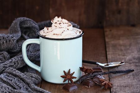 El esmalte taza de chocolate o café caliente para la Navidad con crema batida, virutas de chocolate, vainilla, especias y bufanda gris contra un fondo rústico. Poca profundidad de campo con enfoque selectivo en la bebida.