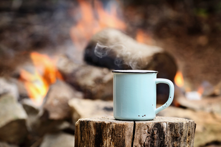 Blue enamel cup of hot steaming coffee sitting on an old log by an outdoor campfire. Extreme shallow depth of field with selective focus on mug.