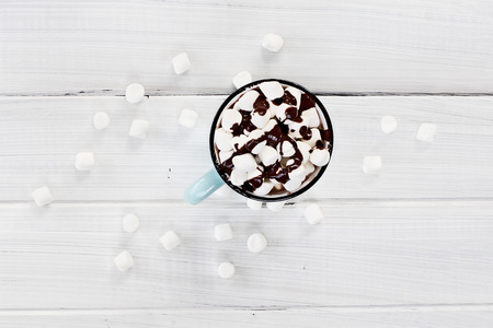 up view: Overhead view of a cup of hot chocolate with marshmallows drizzled with chocolate sauce.