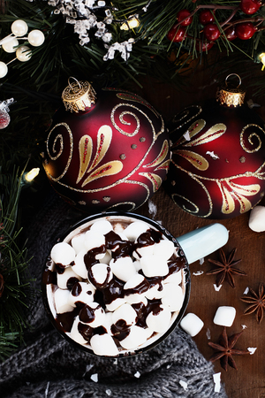 bough: Enamel cup of hot cocoa for Christmas with mini marshmallows and garnished with chocolate sauce.  Surrounded by warm gray scarf, ornaments, pine bough and spices against a rustic background. Image shot from above.