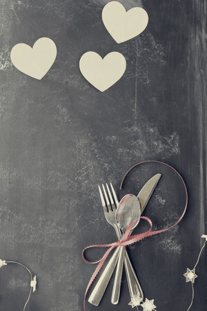 aniversario boda: Top view of Valentines day dinner table setting with cutlery over a rustic blackboard background with wooden cut out hearts and fairy lights. Instagram type filter.