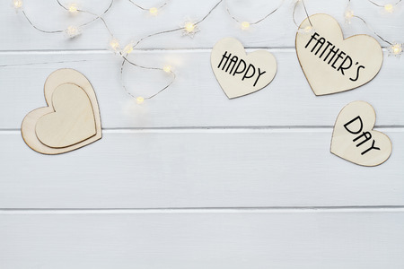 Overhead view of wooden hearts and fairy lights with message Happy Father's Day over a flat wood table top background with copy space available. Archivio Fotografico