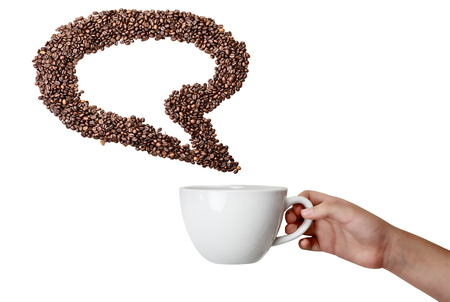 Isolated woman's hand holding cup and coffee bean thought speech bubble over white background with room for copy space. photo