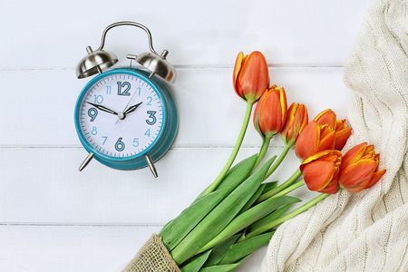 Alarm clock with a beautiful bouquet of tulips and a cozy blanket shot from above in a flatlay style over a wood table top. Daylight savings time concept. Stock Photo