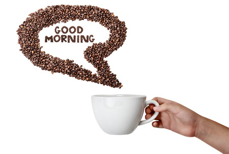Isolated womans hand holding cup and coffee bean thought speech bubble over white background with room for copy space.