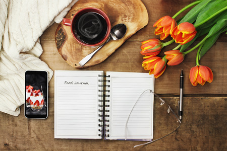 Overhead shot of an open food journal book with cell phone, coffee and flowers over a wood table top ready to plan diet. Flat lay top view style. Фото со стока - 71882327