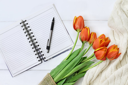 Overhead shot a bouquet of orange and yellow tulips and a cozy knit throw blanket over white wood table top with an open book and pen ready to journal. Flat lay top view style. Stock Photo