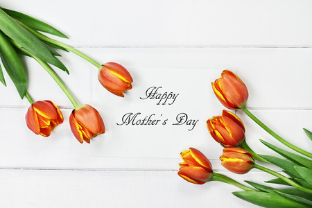 Overhead shot a bouquet of orange and yellow Spring tulip flowers and Happy Mothers Day paper card over white wood table top. Flat lay top view style. Stock Photo