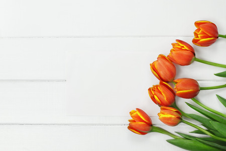 Overhead shot a bouquet of orange and yellow Spring tulip flowers and blank paper card for Mothers or Womens Day over white wood table top. Flat lay top view style.