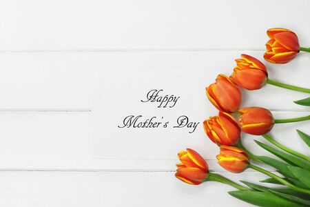 Overhead shot a bouquet of orange and yellow Spring tulip flowers and Happy Mothers Day card over white wood table top. Flat lay top view style.