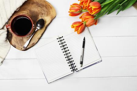 escribiendo: Overhead disparó una taza de café, libro abierto, manta de tirilla de punto y un ramo de flores de tulipán naranja y amarillo sobre la mesa de madera blanca. Estilo plano de la vista superior plana.