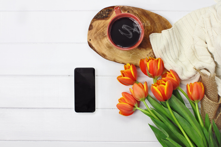 overhead shot: Overhead shot a phone with a hot cup of coffee and a bouquet of tulip flowers with a cozy knit throw blanket over white wood table top. Flat lay top view style.