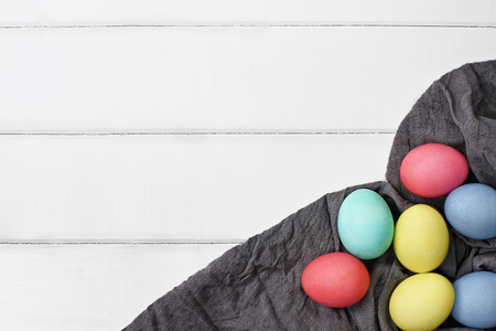 red cloth: Overhead view of colorful Easter eggs over a wood table top with grey fabric. Flat lay style.
