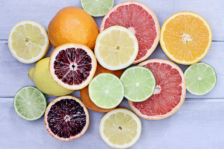 Variety of citrus fruits (orange, blood oranges, lemons, grapefruits, and limes) over a blue wood table top rustic background. Image shot from overhead.