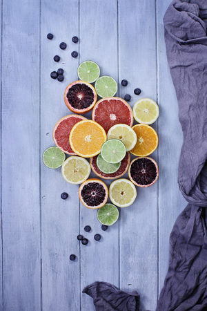 Variety of citrus fruits (orange, blood oranges, lemons, grapefruits, and limes) with blueberries with grey fabric over a blue rustic wood table top. Image shot from overhead.