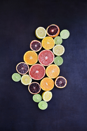 Variety of citrus fruits (orange, blood oranges, lemons, grapefruits, and limes) over a black rustic background. Image shot from overhead. Stock Photo