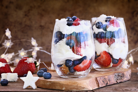 Trifle made with blueberries, strawberries, whipped cream and star shaped pound cake against a rustic background. Perfect for fourth of July. Shallow depth of field with selective focus. Stockfoto