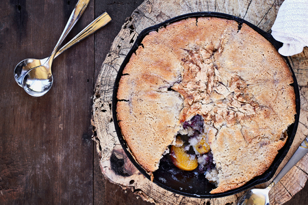 Above image of a blueberry and peach cobbler baked in a cast iron skillet over a rustic wood table top. Image shot from overhead. Perfect dessert for spring or summer.