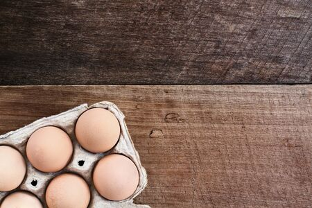 close range: Farm fresh organic brown chicken eggs from free range chickens with in a paper carton over a rustic wooden background.