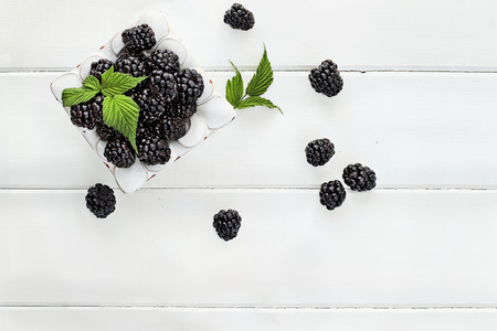 Overhead shot of fresh blackberry fruit over white wood table top. Room for copy space. Standard-Bild