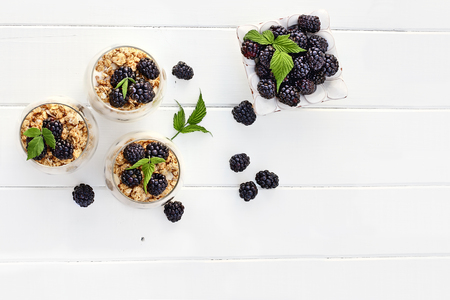 Blackberry parfaits made with Greek yogurt, granola and fresh blackberries shot from overhead over white wood table. Room for copy space.