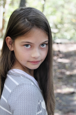 Young pre-teen kid with long hair looking directly into the camera. photo