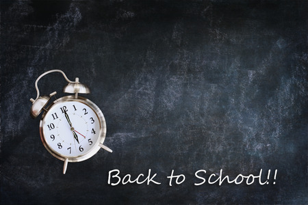 back in an hour: Dusty blank school chalkboard or blackboard with clock and back to school message. Room for copy space.