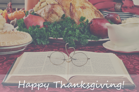 Filtered image of an open Bible with glasses lying on a holiday dinner table with prepared turkey and fixings in background and  Happy Thanksgiving text in foreground. 写真素材