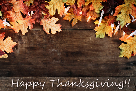 Rustic fall background of autumn leaves and decorative lights with Happy Thanksgiving text over a rustic background of barn wood. Image shot from overhead. Imagens