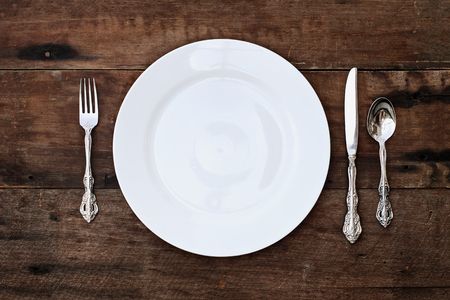Place setting of a dining set of an empty plate with spoon, fork and knife over a rustic old wooden background. Image shot from overhead.