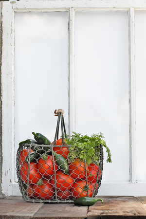 self sufficient: Ingredients for homemade salsa in an old country basket sitting in front of a window.