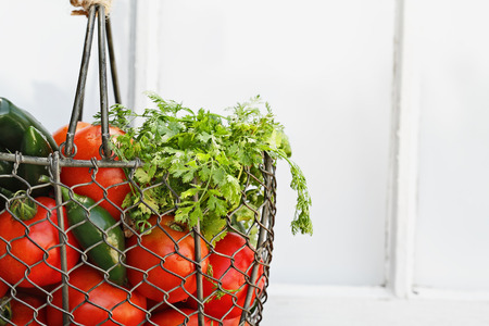 Ingredients for homemade salsa in an old country basket sitting in front of a window. Shallow depth of field. Stock Photo