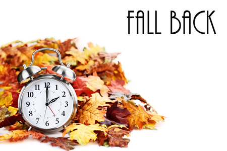 Alarm clock in colorful autumn leaves isolated against a white background with light shadow and shallow depth of field. Daylight savings time concept.