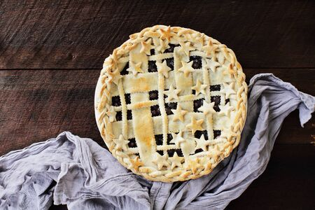 Top view of a blueberry pie with lattice and stars crust over a rustic wooden background.