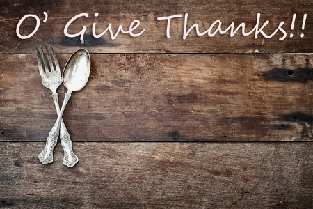 Antique silverware spoon and fork with O Give Thanks text over a rustic old wooden background. Image shot from overhead.