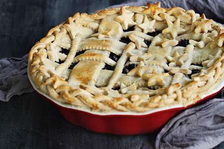 Moody shot of a blueberry pie with lattice and stars crust in a red pie pan against a rustic background.