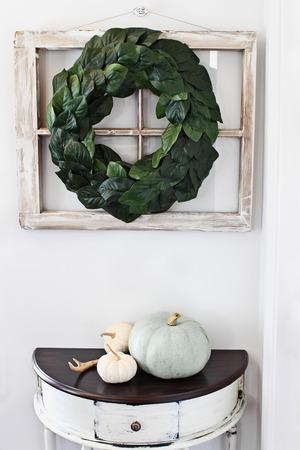 自家製のマグノリアの葉の花輪で飾られた古い農家の窓は、家宝カボチャと素朴な半月テーブルの上の内壁に掛け 写真素材