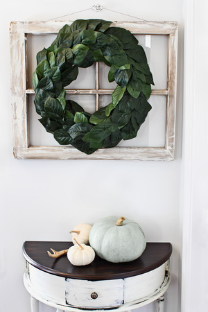 Old farmhouse window decorated with a homemade Magnolia leaf wreath hung on an interior wall over rustic half moon table with heirloom pumpkins Imagens