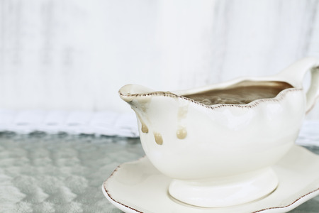 Messy gravy boat with drips of gravy running down the side ready for Thanksgiving Day. Extreme shallow depth of field.